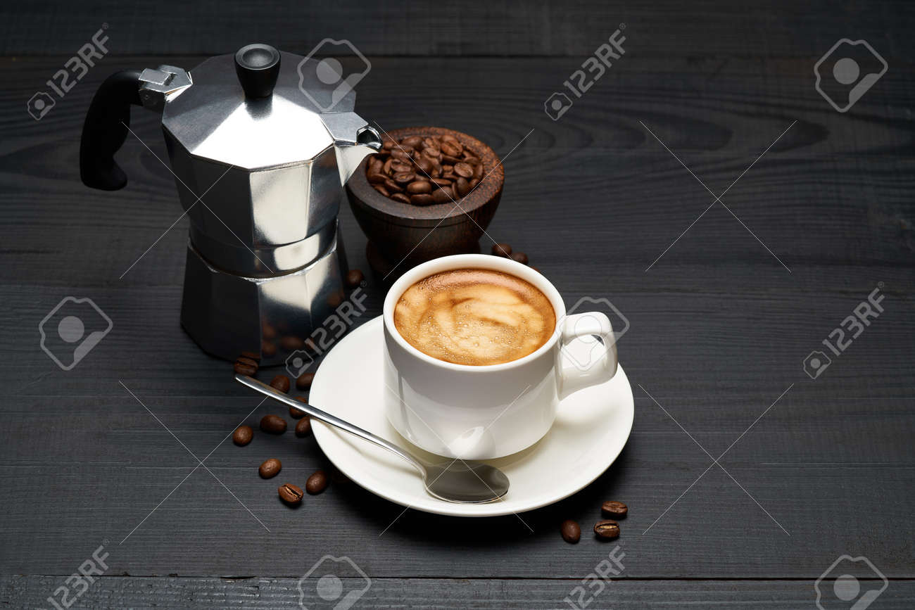 Cup of espresso coffee and mocha coffee maker on dark wooden background - 169835568