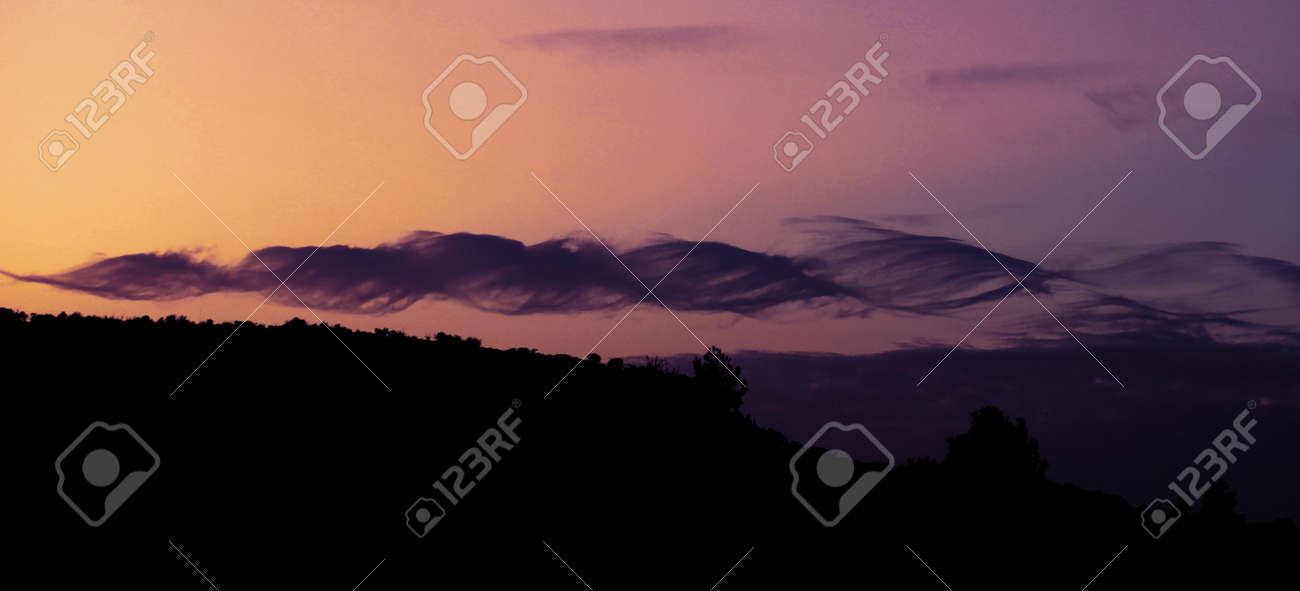 Beautiful dramatic sky with spiral purple clouds on dark mountains background, horizontal banner - 161142972
