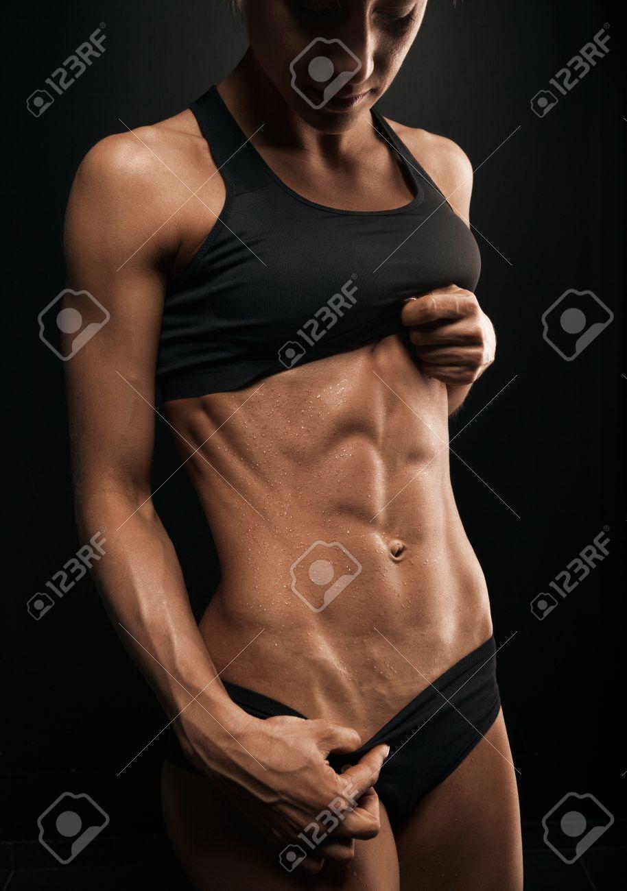 Schöne sportliche Frau schüttelt den Bauchmuskeln auf dunklem Hintergrund