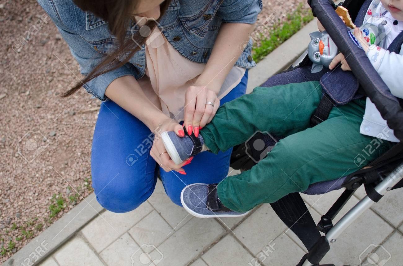 Parc Dans Mère Jeune Petites Le Chaussures Son Fils À Met Des f76vgIYby