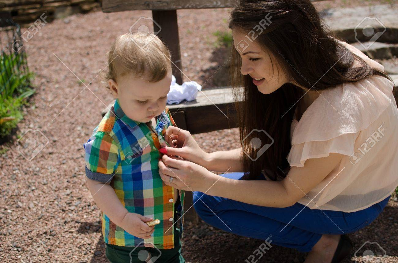 b509d248386a Young Mother Changes Clothes For Her Small Baby Boy Stock Photo ...