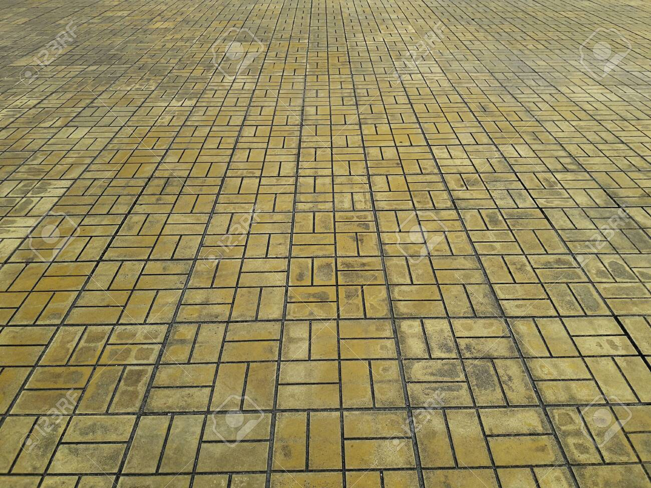 The pattern of tiles on the floor yellow cobblestone road - 128553086