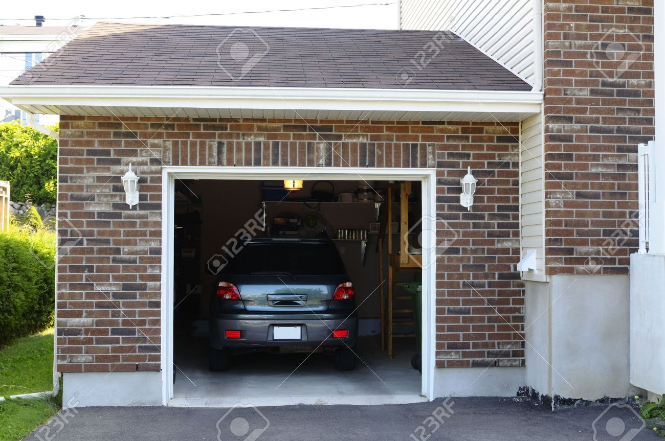 Suv Car In A Garage Next To The Entrance To A House Stock Photo