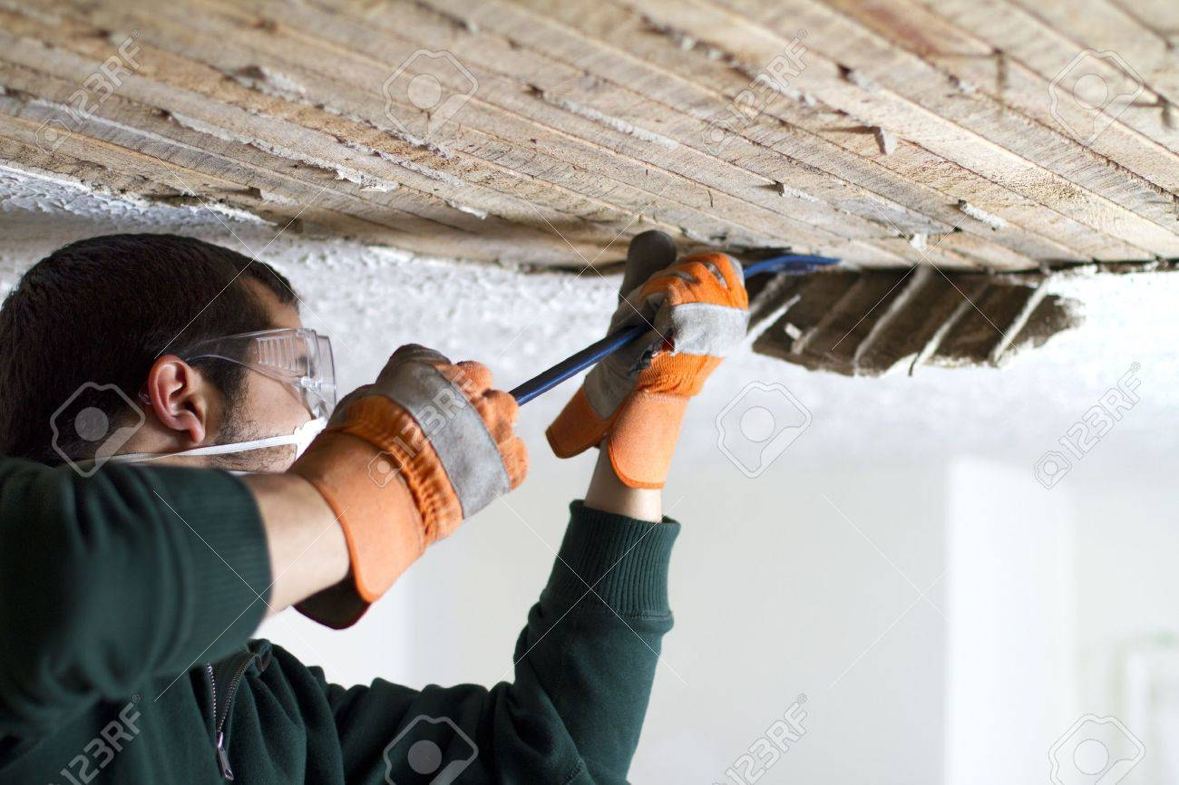 Ceiling Scrape man scraping plaster off of ceiling lathe with a crowbar Stock Photo - 18956893