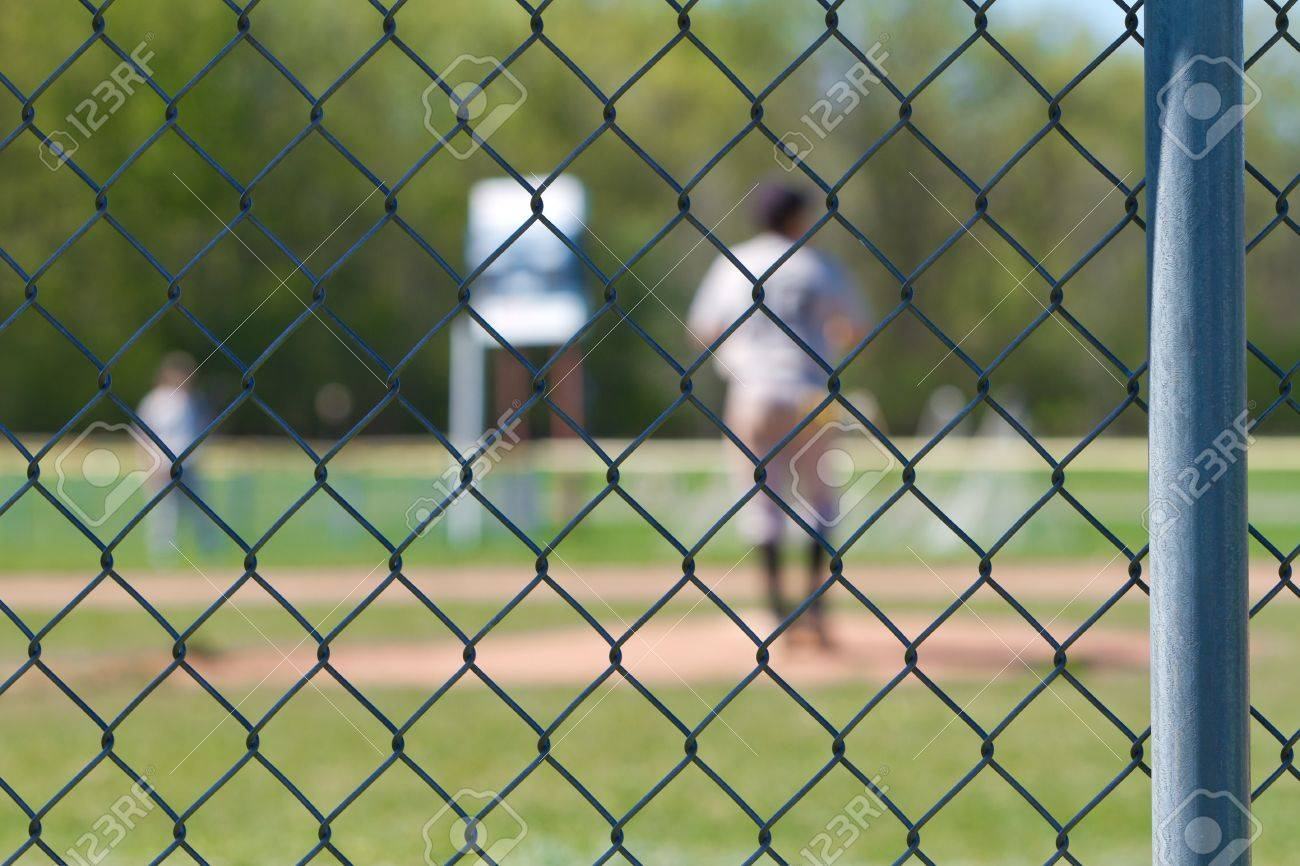 a chain link baseball fence with a blurred out backdrop of a baseball game going on. Stock Photo - 19238214
