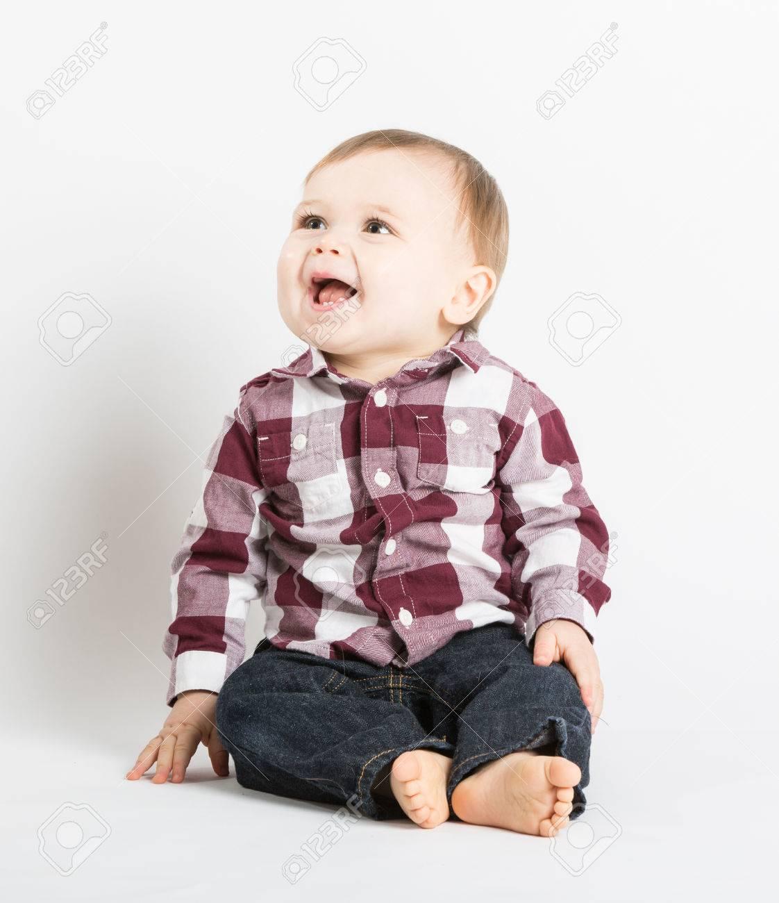 Foto de archivo - Un bebé de 1 año linda se sienta en el estudio blanco con  pantalones vaqueros y un rojo de franela blancos mirando y riendo fuera de  ... f0a70e11abd