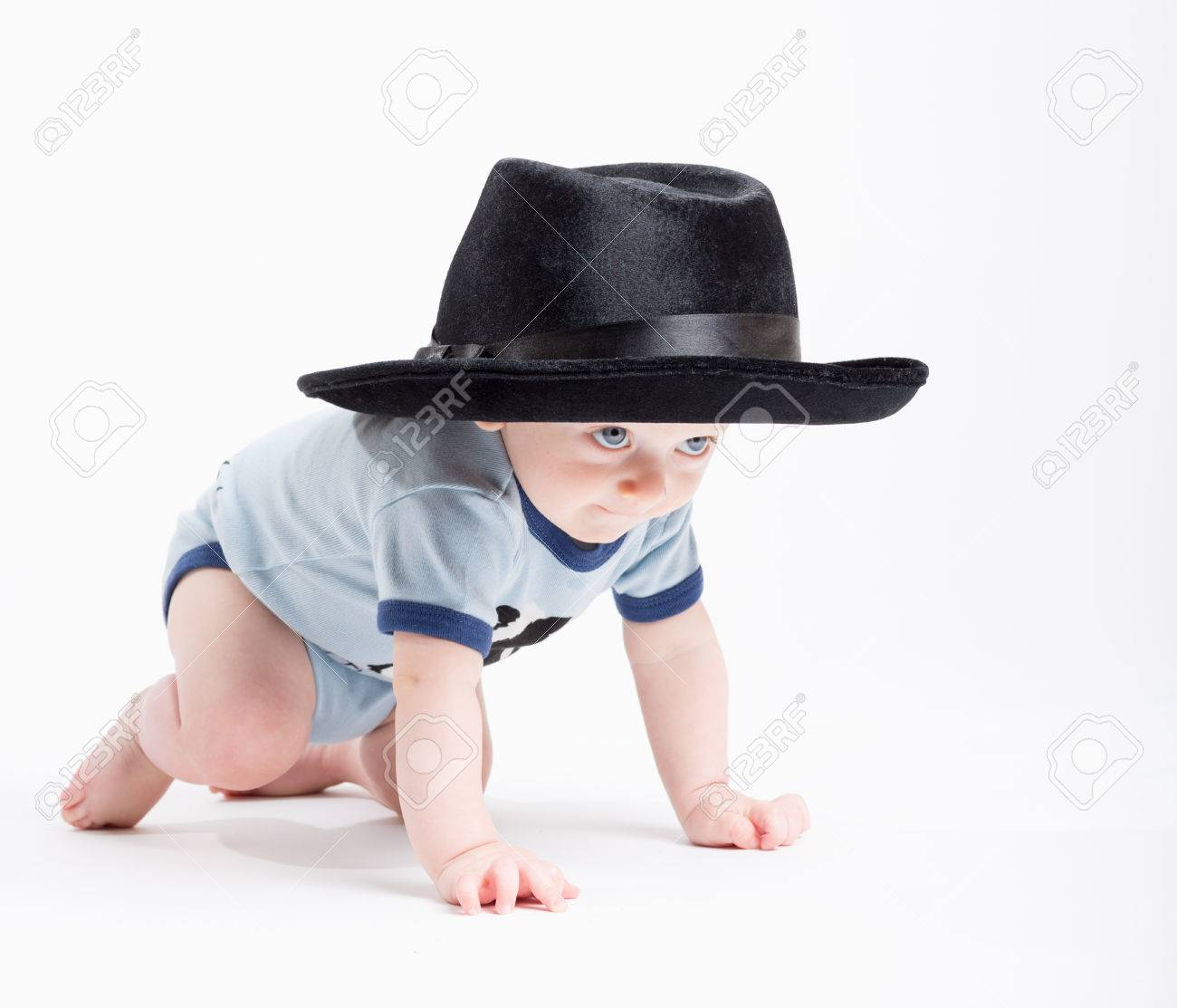 a 6 month old baby crawls on a white background wearing a black fedora hat  Stock cc2160505f0