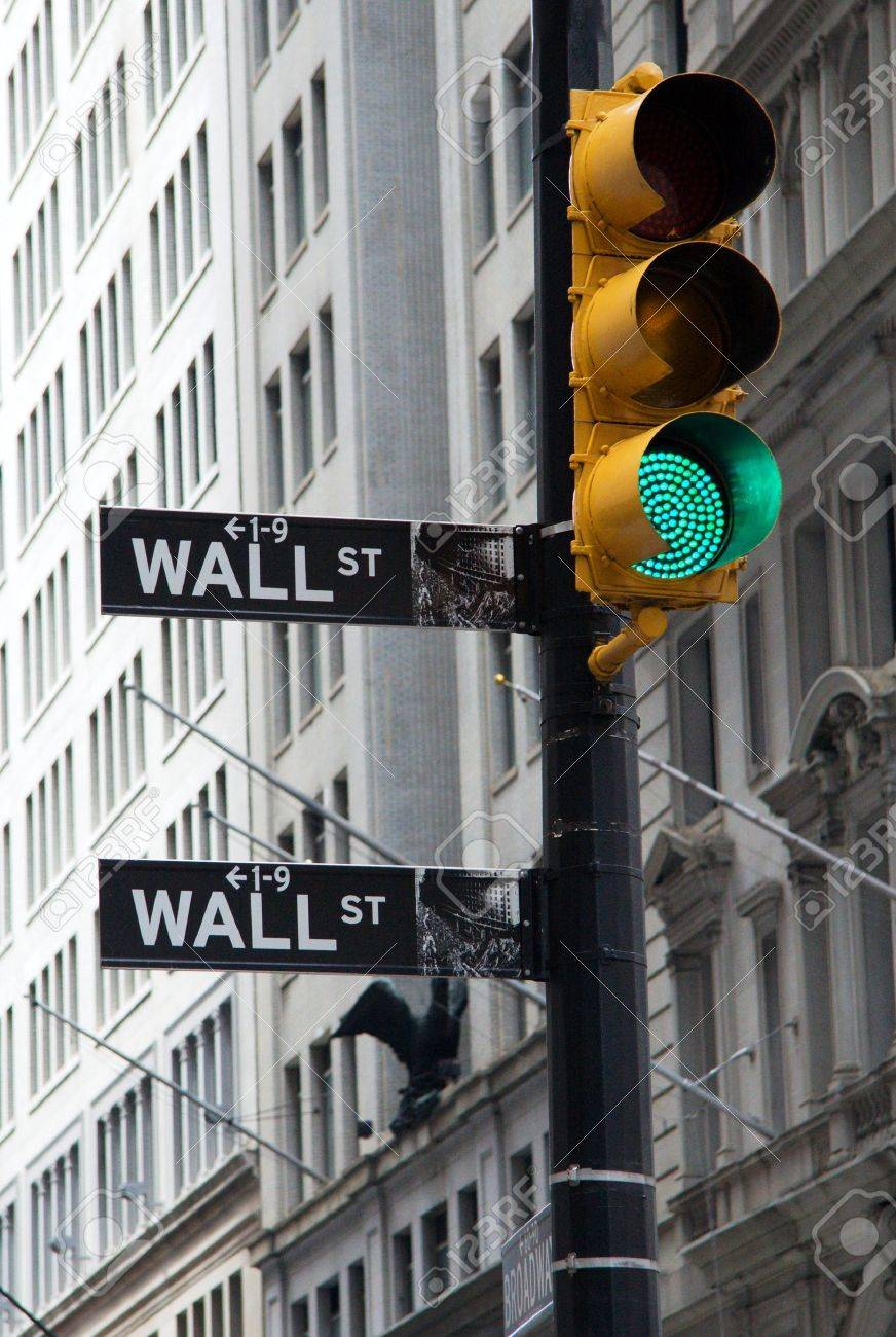 NEW YORK - JUNE 20: A symbolic photo of Wall street signs with a green traffic light on June 20, 2011 in New York. The green light is a symbol of prosperity. Stock Photo - 13365110