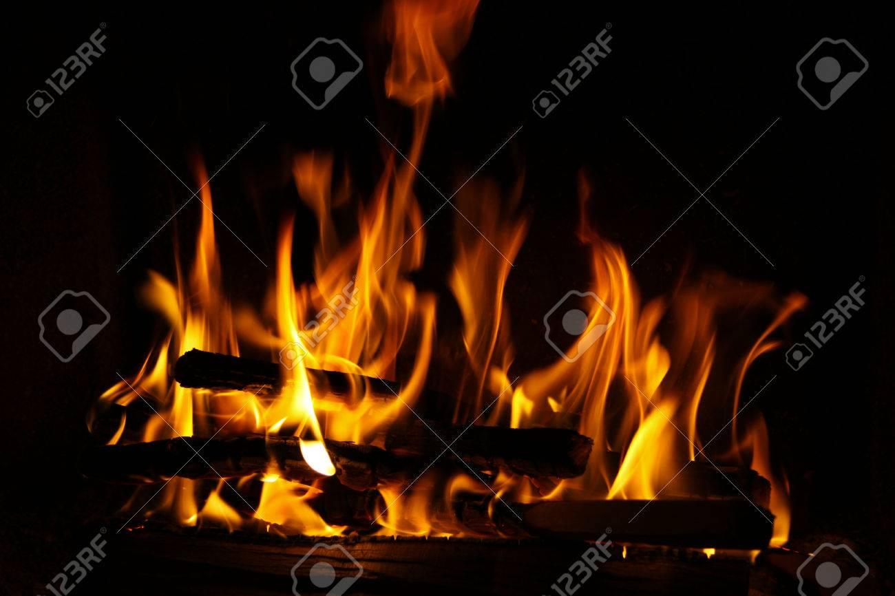Brand in een open haard, vuur vlammen op een zwarte achtergrond ...