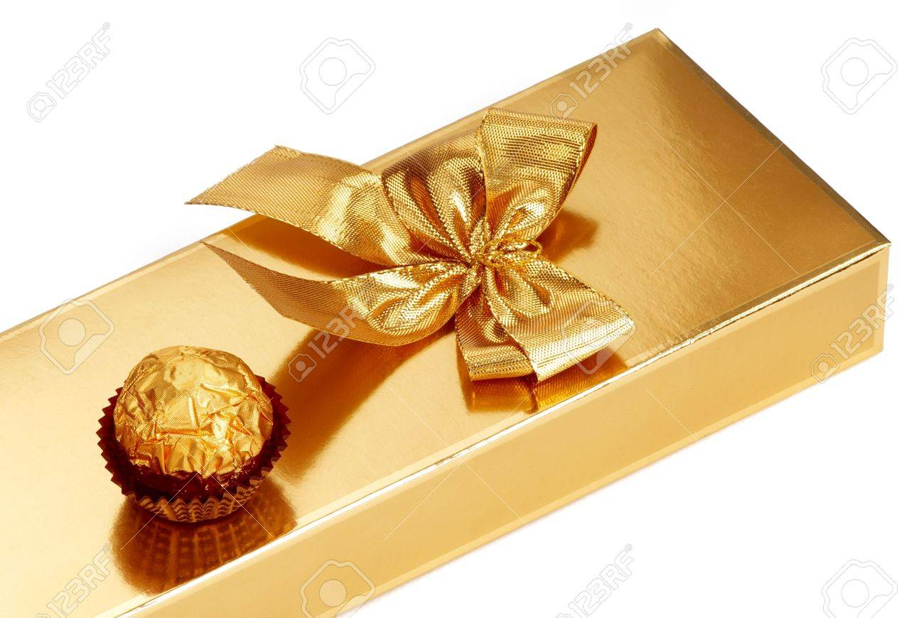 A Gold Boxed Gift With Gold Ribbon And Chocolate. Stock Photo ...