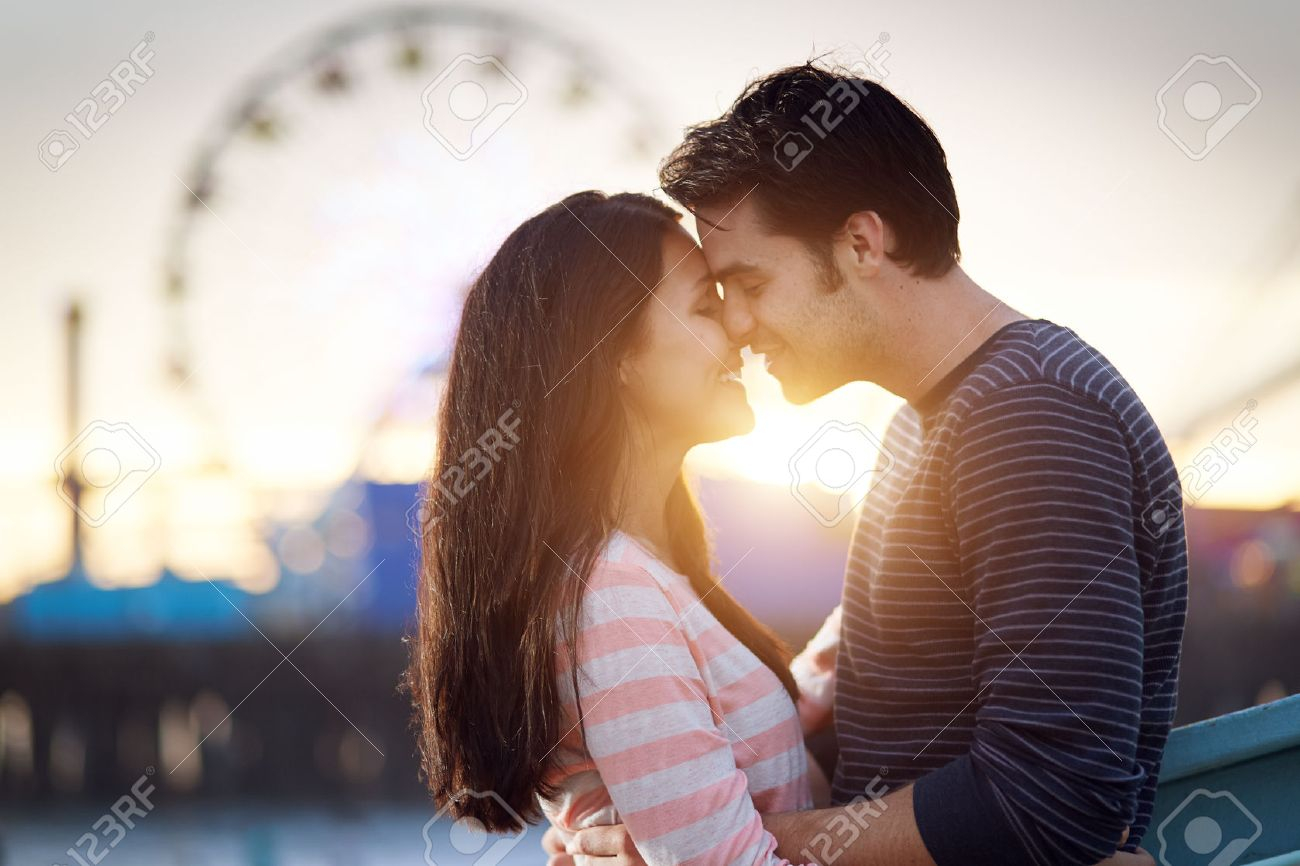 romantic couple in front of santa monica amusement park at sunset Stock Photo - 23289160