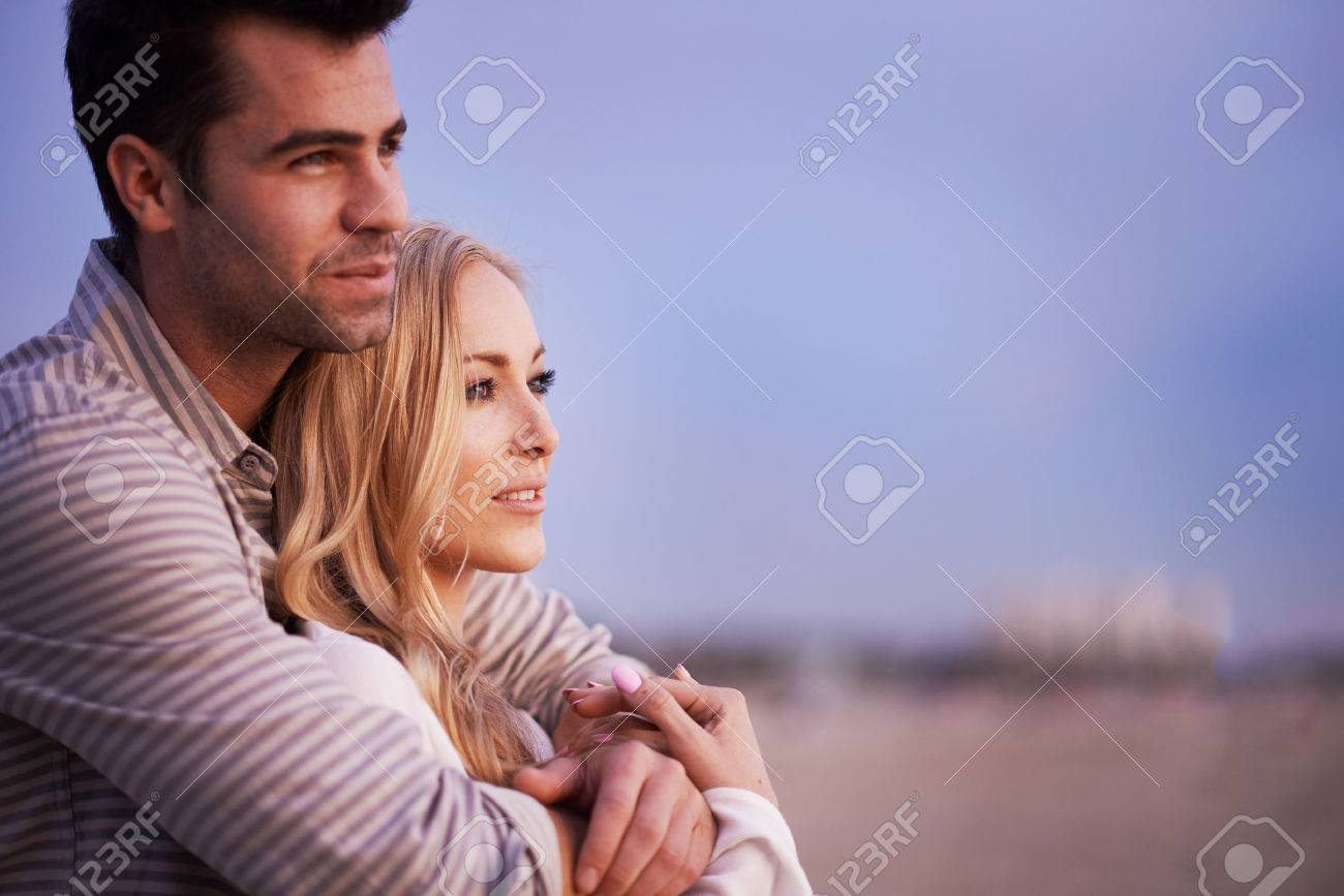 couple on beach at twilight looking outwards - 36931582