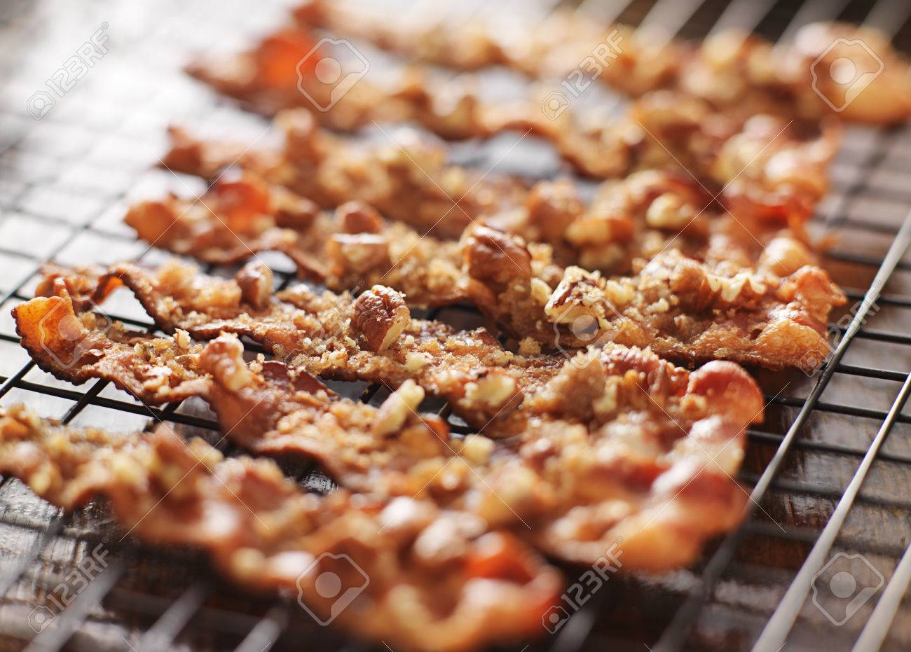 stock photo candied bacon with pecans and brown sugar cooling on baking rack