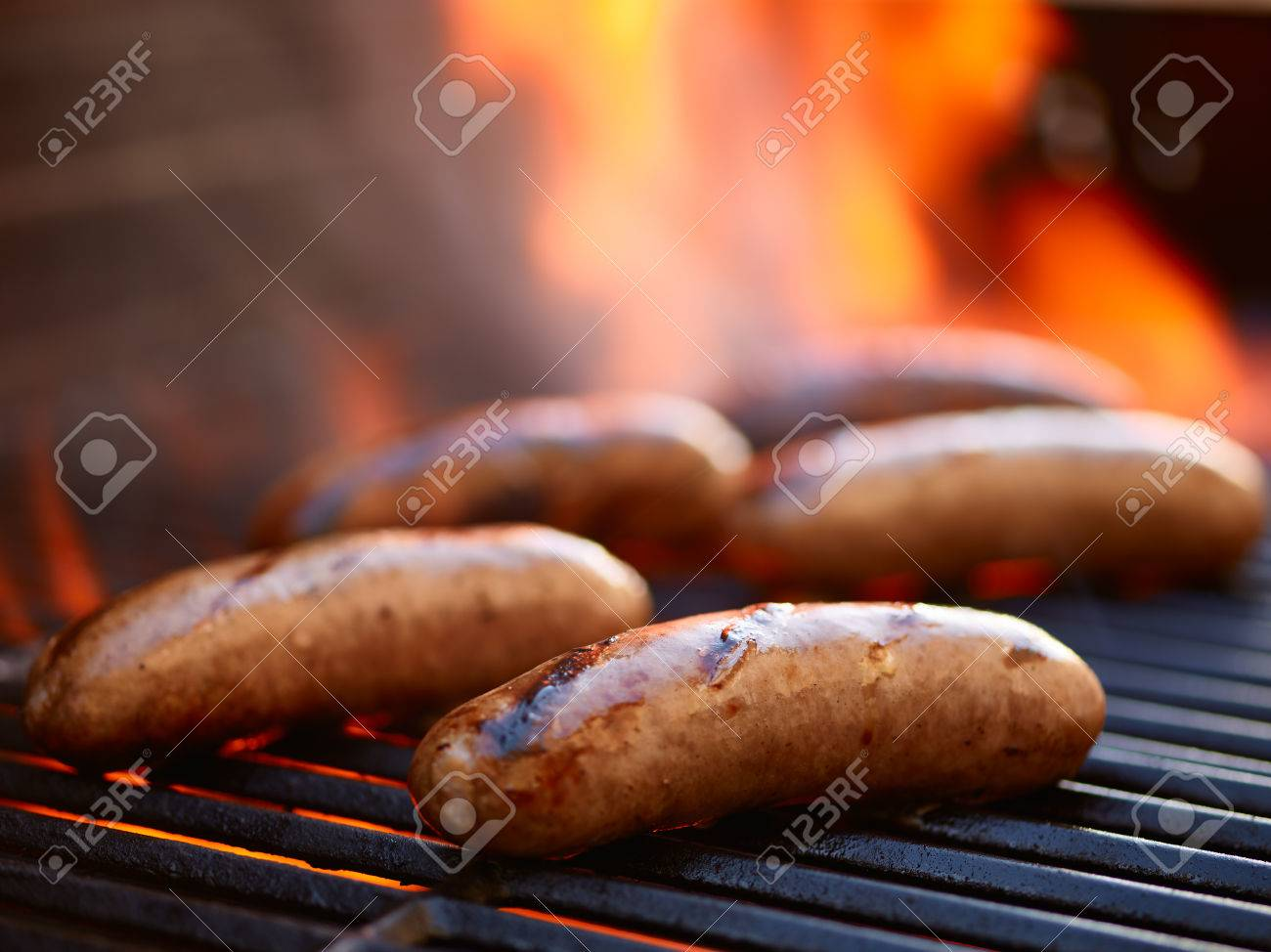 grilling bratwurst sausages over flaming grill - 55030127