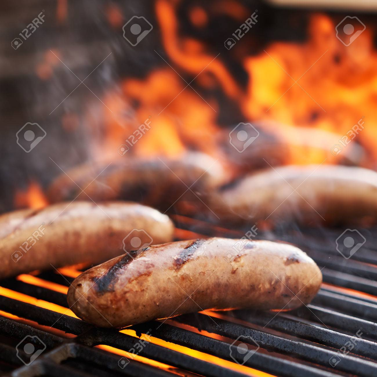 bratwurst sausage barbecue cooking on grill top with flames - 55030137