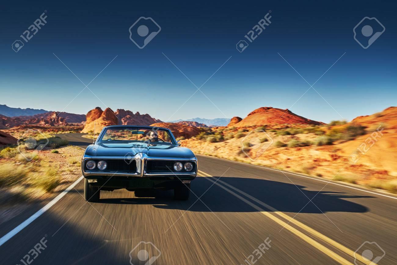 man driving vintage car through desert - 68020882