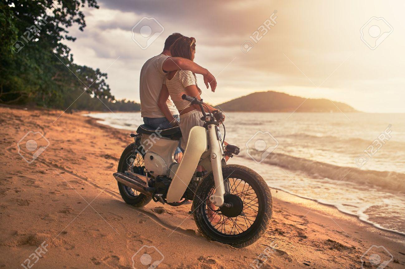 coppia romantica seduto sul moto d'epoca a guardare il tramonto a Koh Samui Thailandia Archivio Fotografico - 73081777