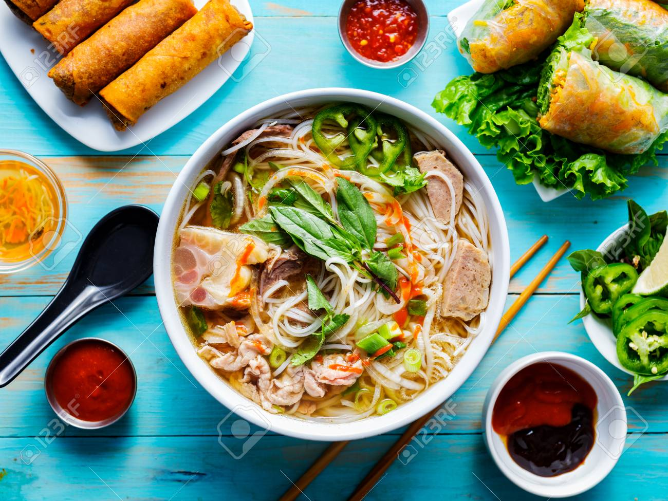 colorful vietnamese pho bo with beef and spring rolls - 118469069
