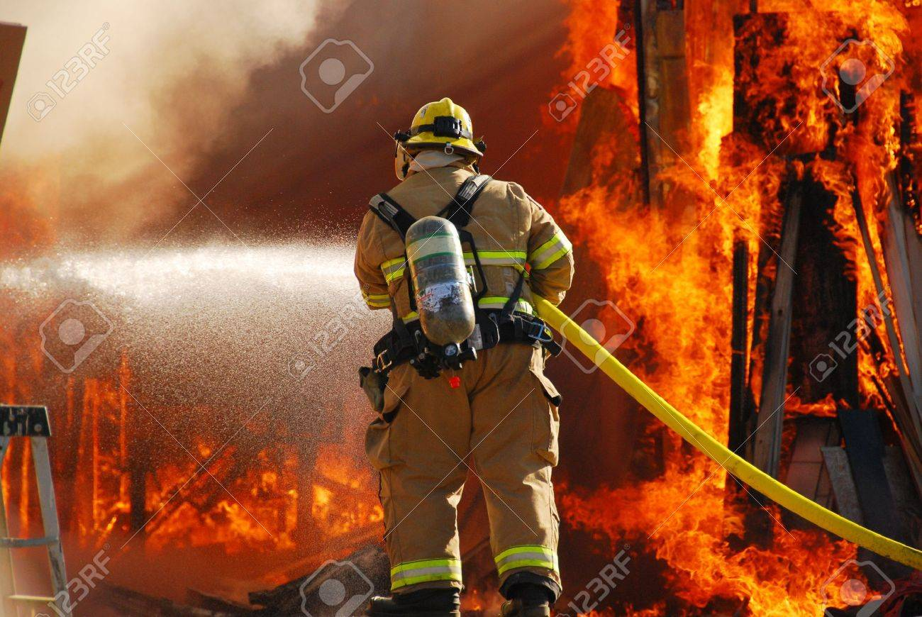 Fire fighter attacking a fully involved shop fire. Stock Photo - 10734009