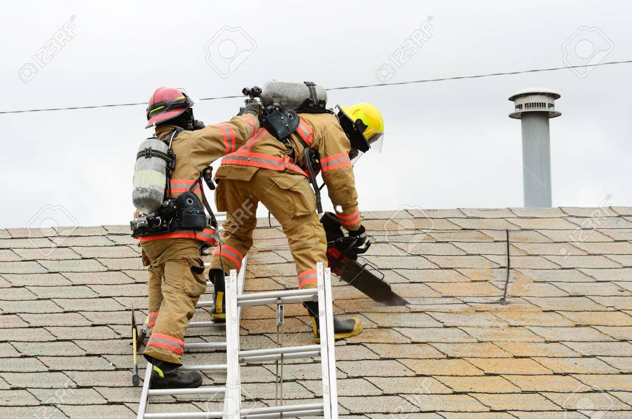 Roseburg, OR USA - July 21, 2011: Roseburg Fire Fighters participating in a vertical ventilation drill at a old hotel. Stock Photo - 11970698