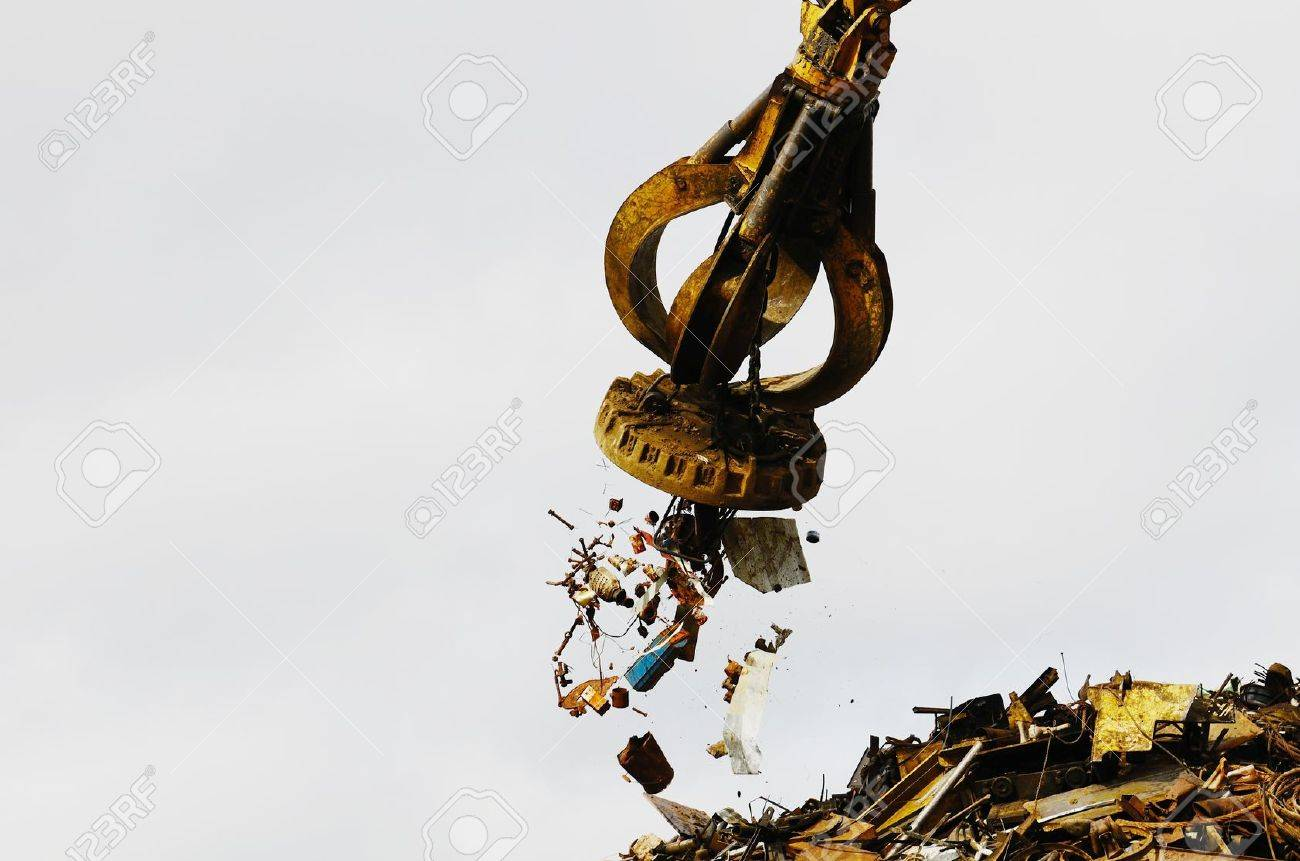 Large tracked excavator working a steel pile at a metal recycle yard with a magnet. - 13749109
