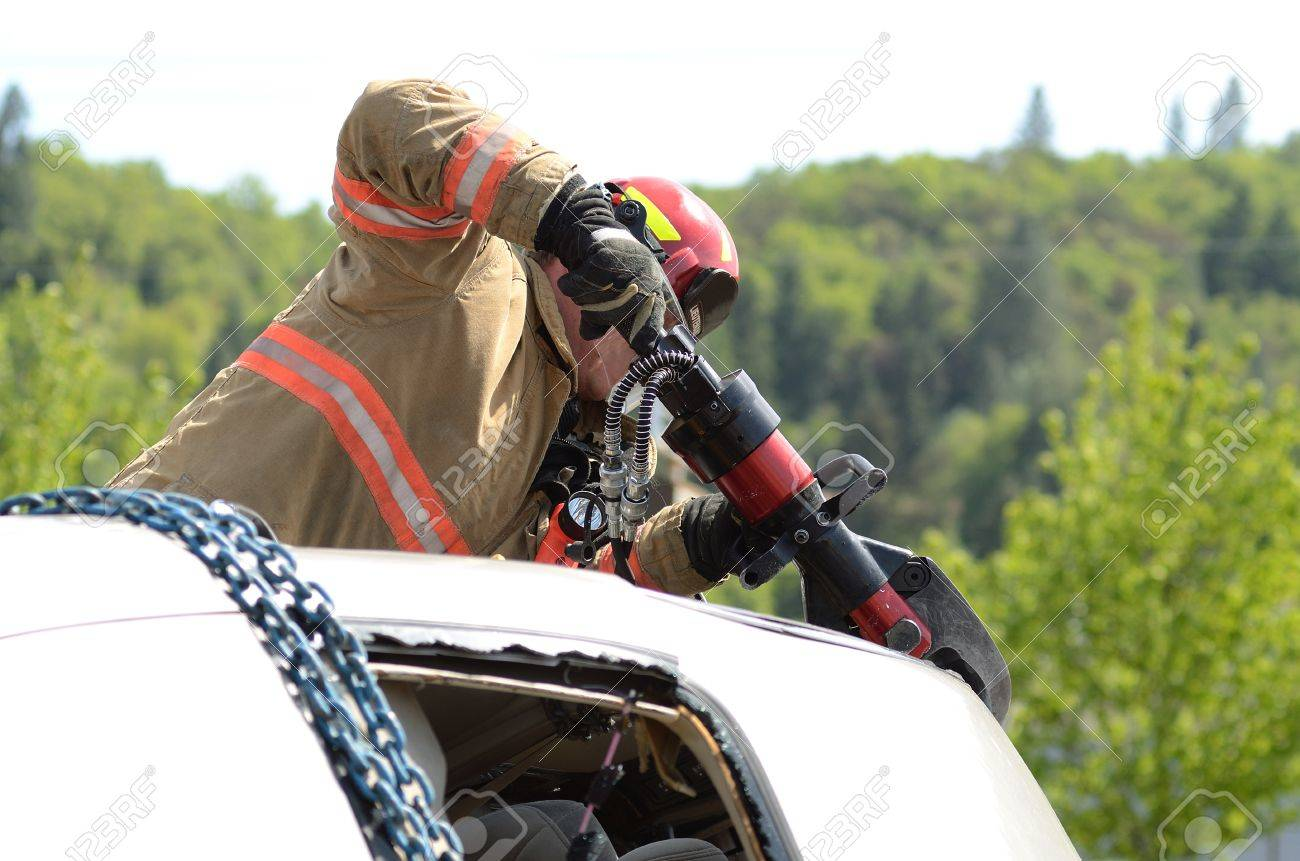 Firefighters working on an auto vehicle extrication with a hydraulic