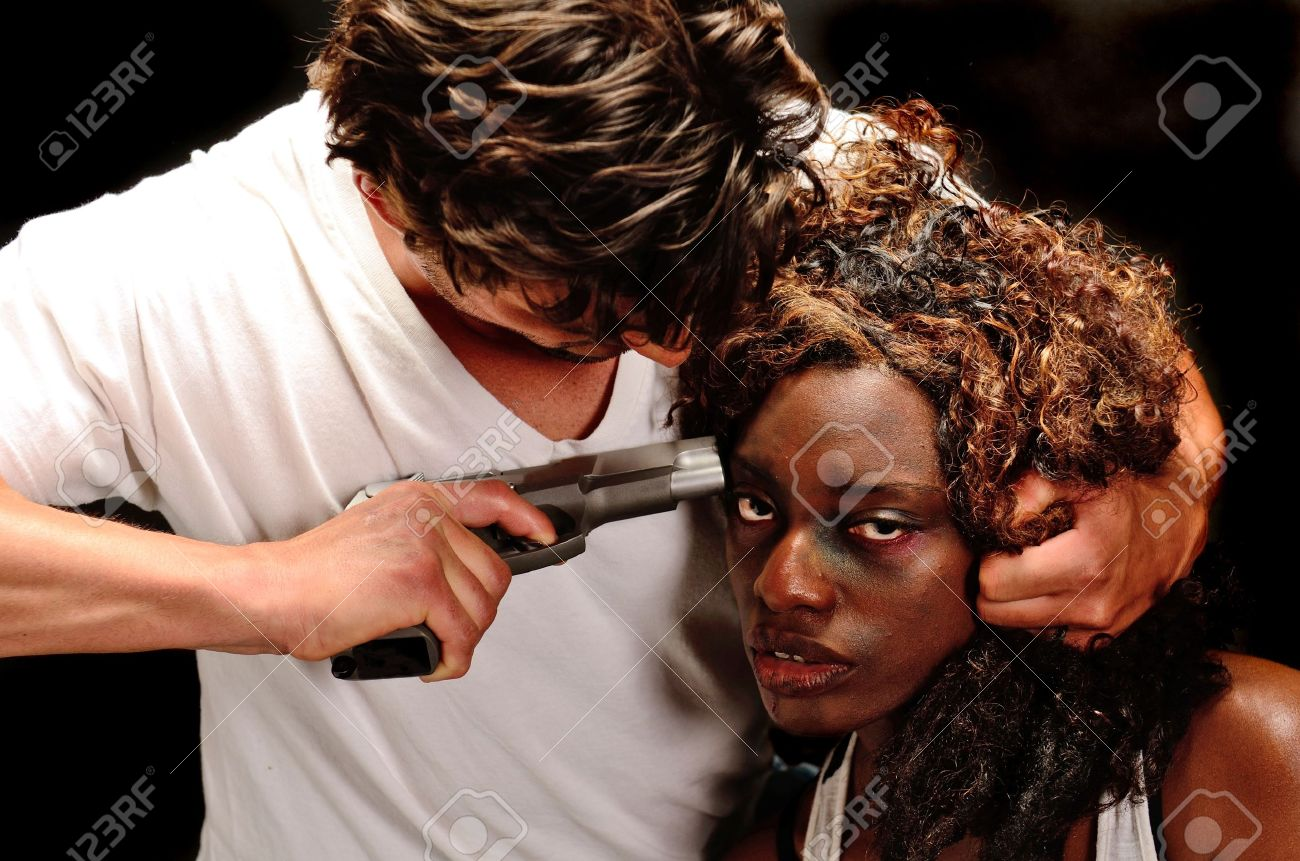 A young beautiful african american female and a handsom young white italian male pose showing domestic violence in this dark photo shoot against black Stock Photo - 20638216