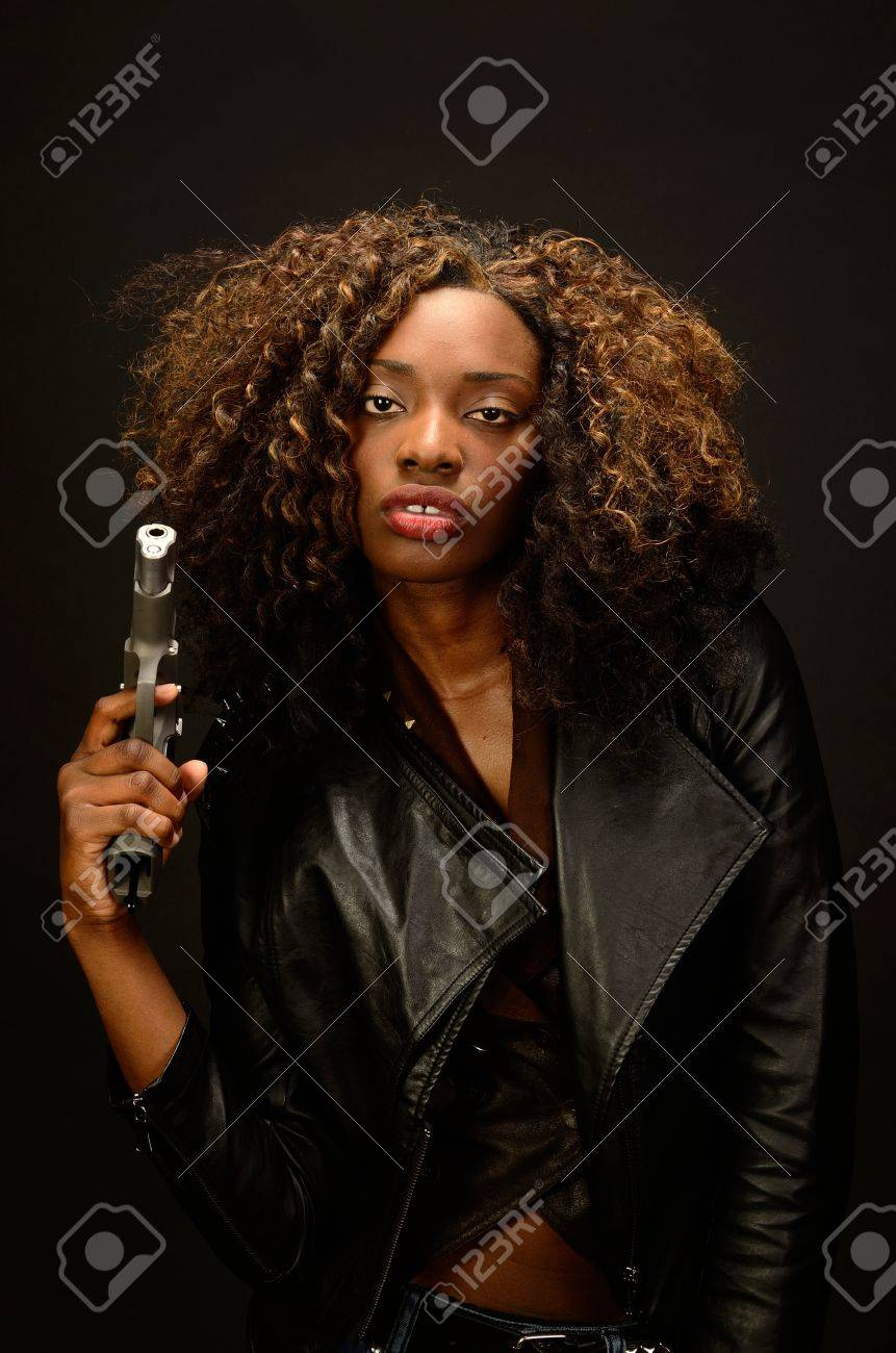 A young beautiful african american female holds a semi automatic pistol during this dark photo shoot against black Stock Photo - 20638204