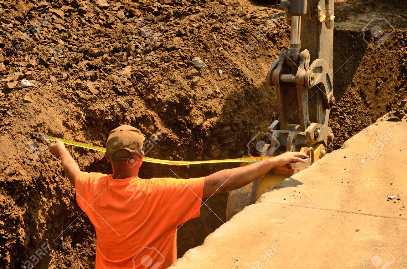 A backhoe and crew dig a utility trench for gas and other electrical