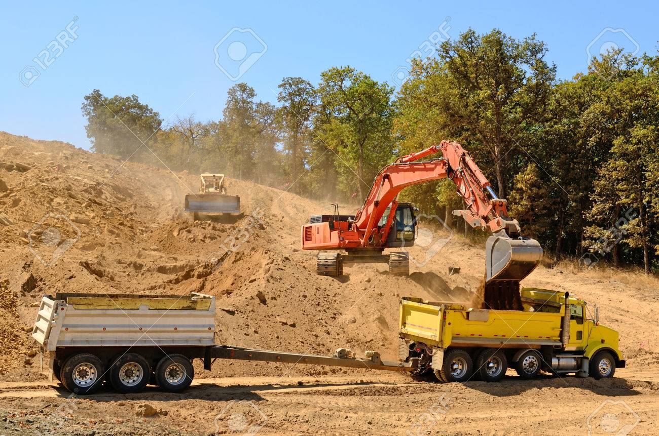 large track hoe excavator filling a dump truck with rock and