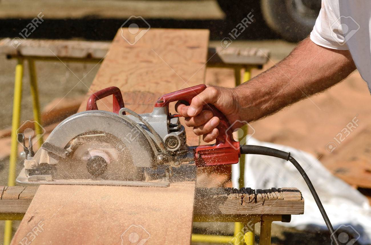 building contractor worker using hand held worm drive circular saw to cut boards on a new