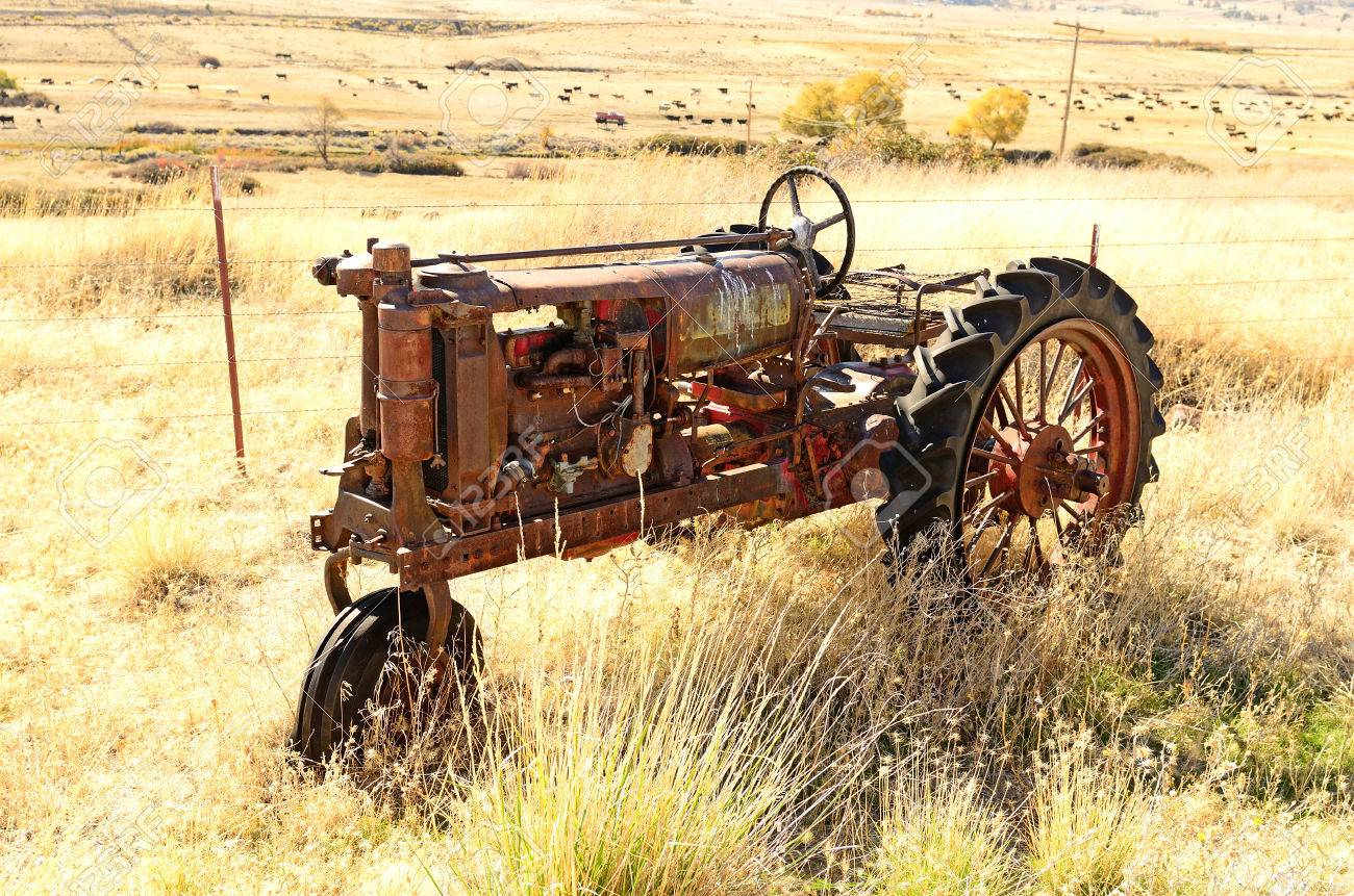 An old three wheel tractor sits next to a large cattle ranch in northern California Stock Photo - 26132391