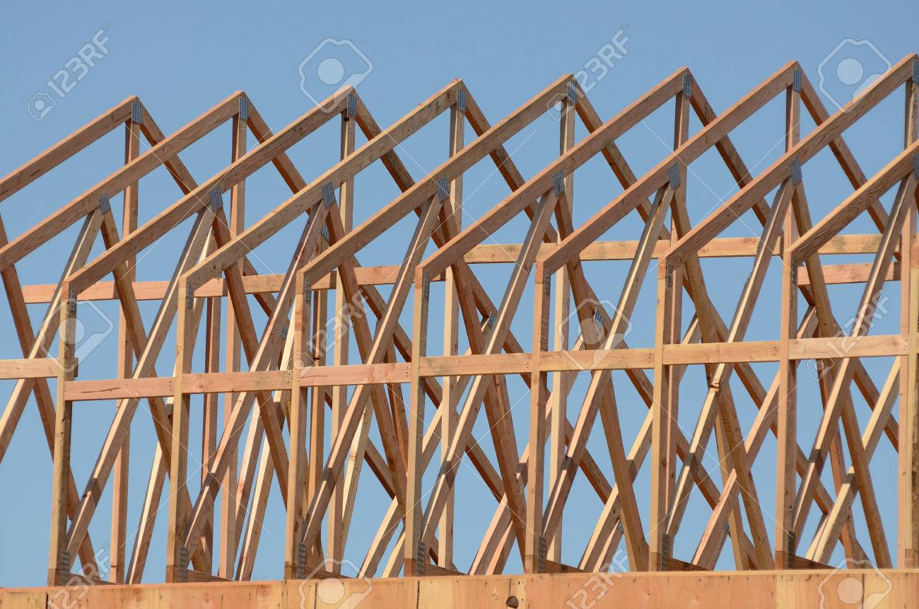 construction framing contractor installing the roof truss system to a new commercial residential development stock photo