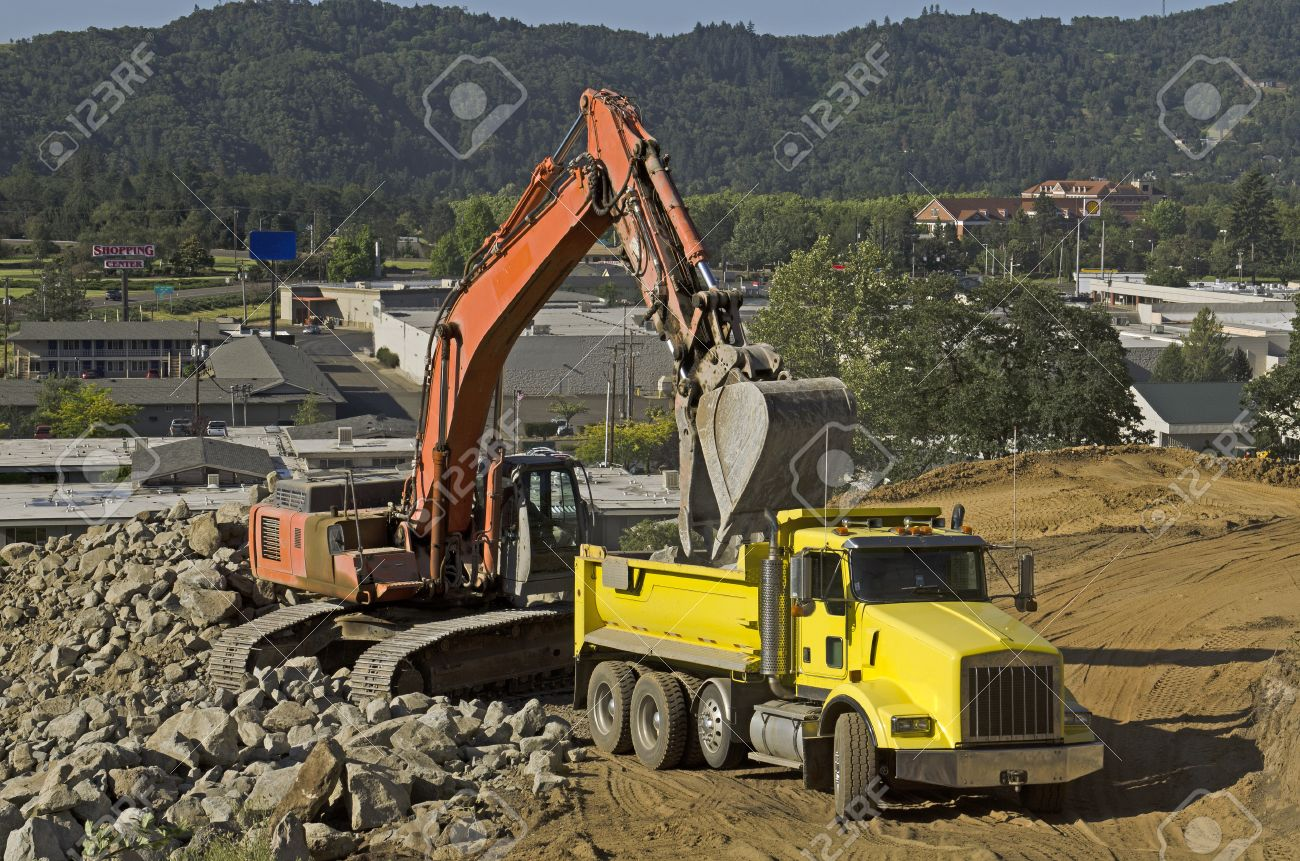 a large track hoe excavator loads a dump truck with dirt and