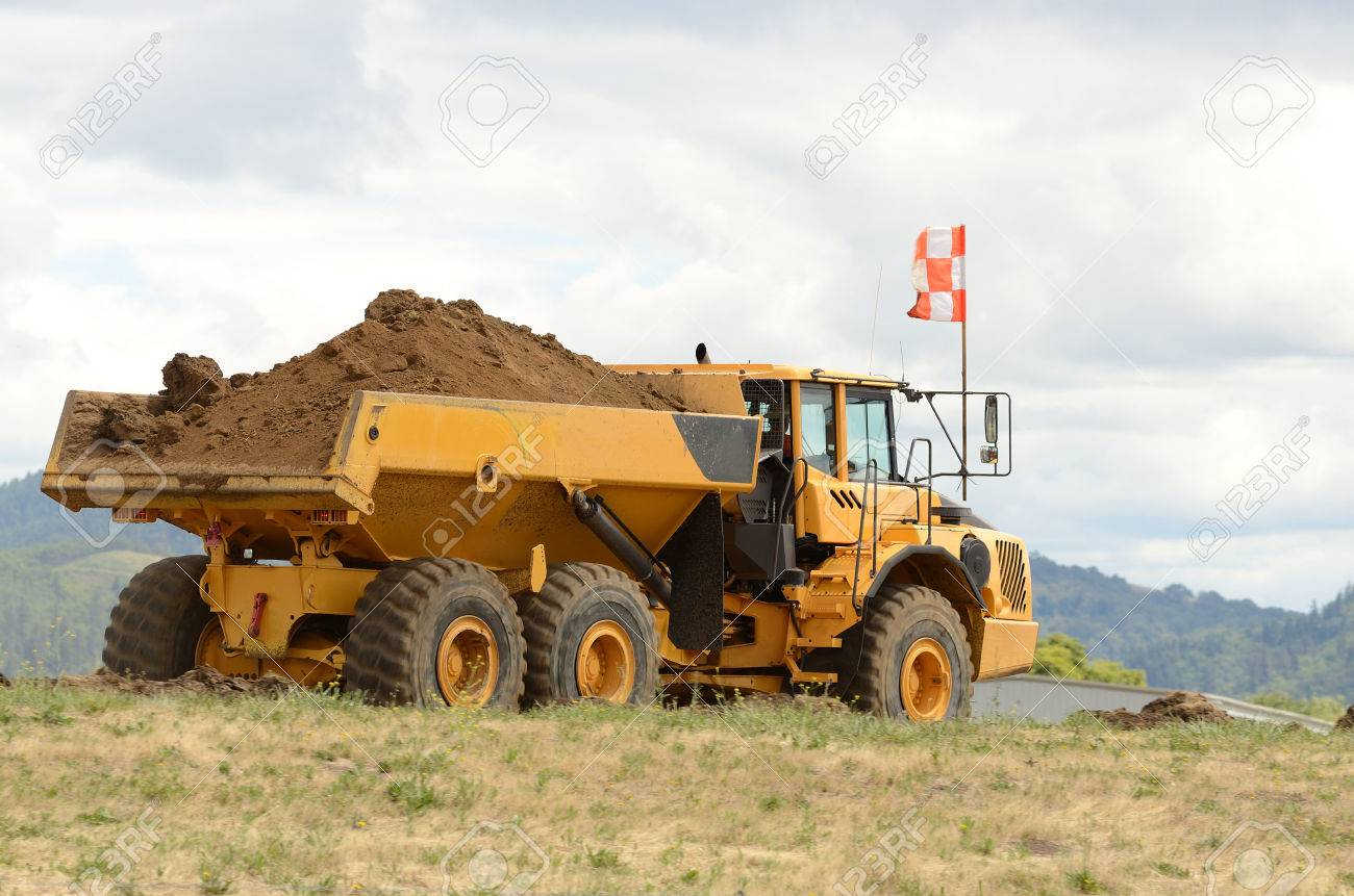 Large dump tractor moving dirt and rocks for a airport runway