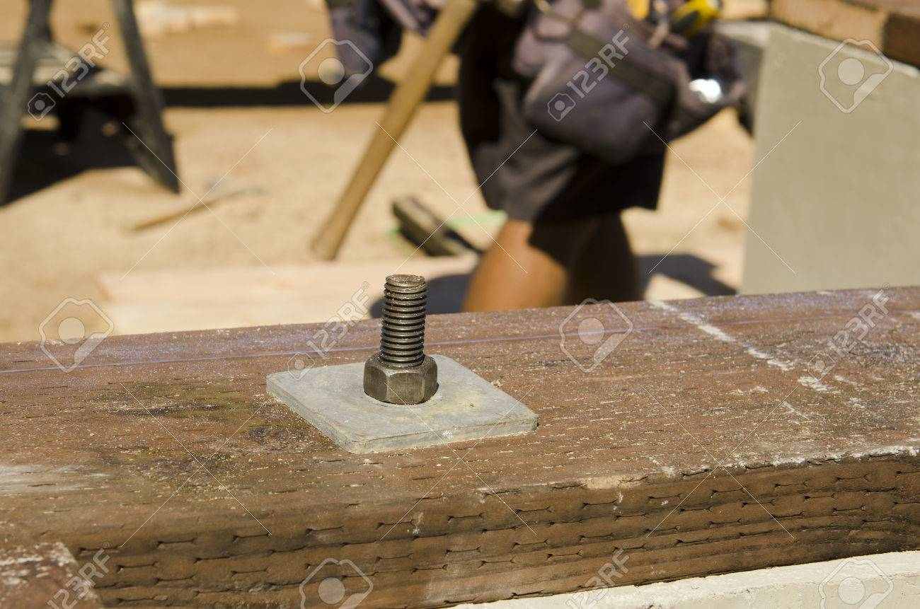 framing contractor using a wrench to tighten down the nut on a pressure treated sill plate