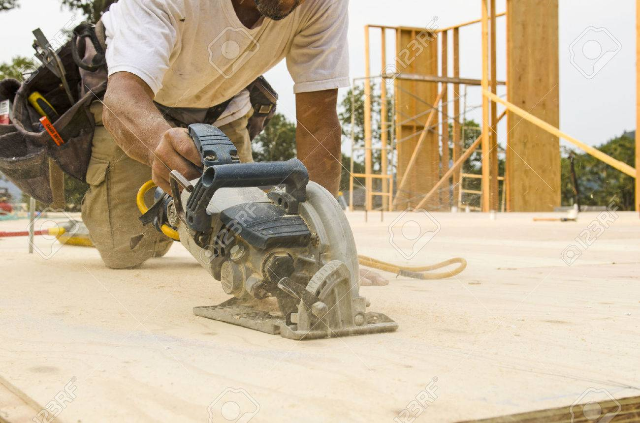 Framing contractor uses a circular had saw to cut and trim plywood framing contractor uses a circular had saw to cut and trim plywood sub floor panels on jeuxipadfo Choice Image
