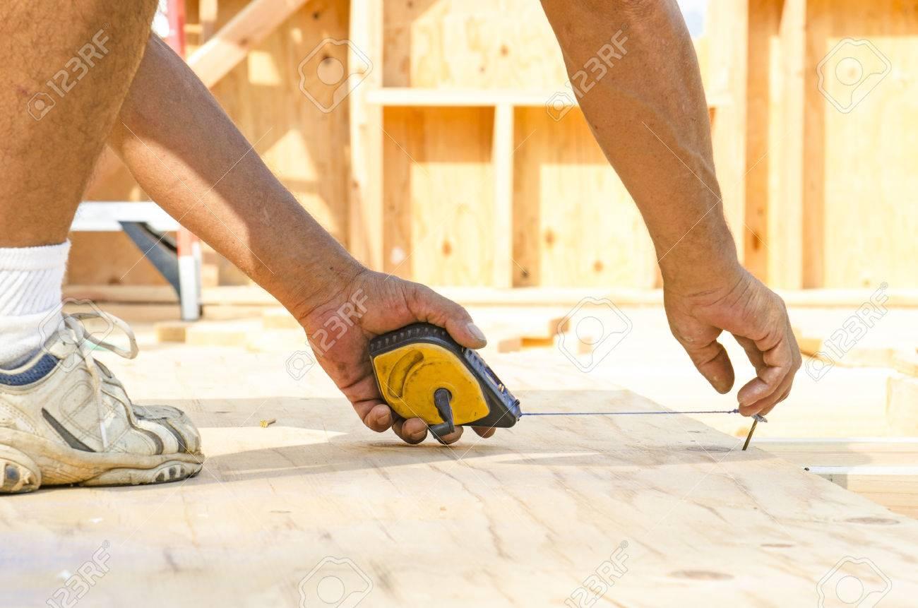 Enmarcando medición contratista y línea de tiza para instalar madera contrachapada sub revestimiento para viga de madera