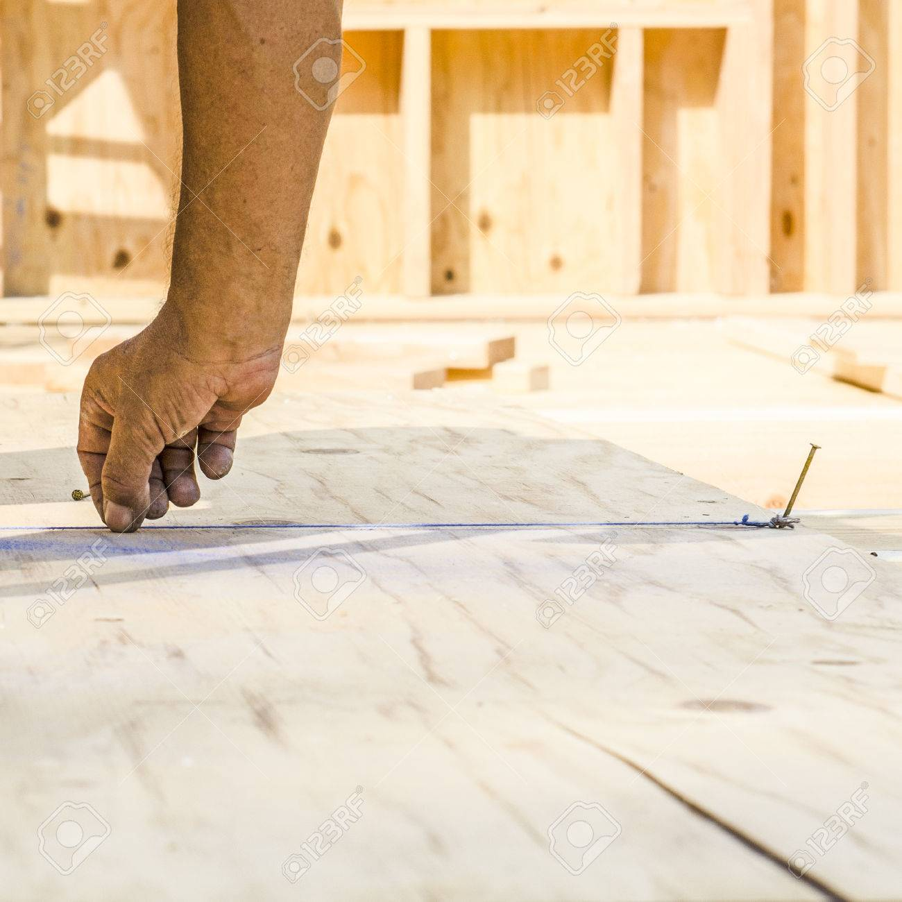 framing contractor measuring and chalk line to install plywood sub siding to wood joist stock photo