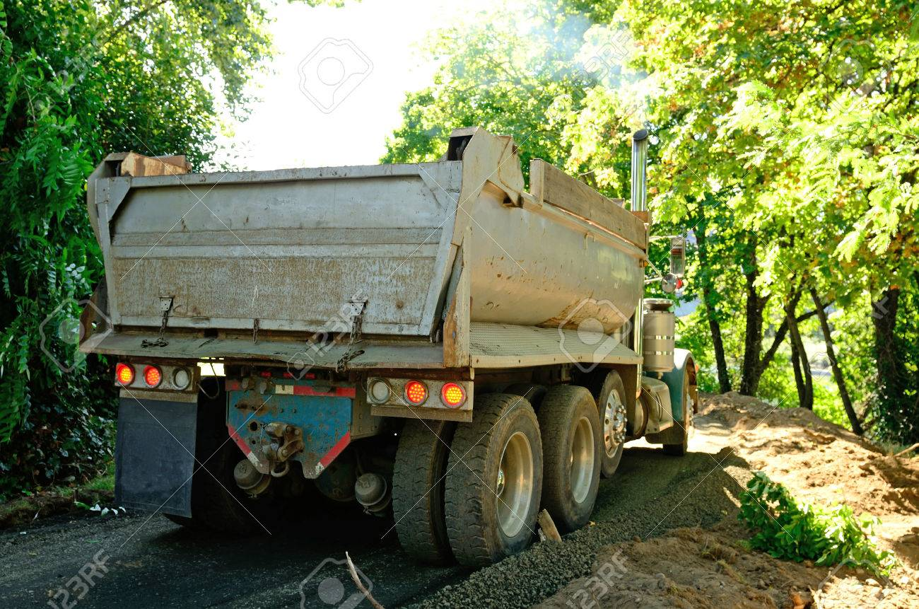 A Dump Truck Unloading Gravel For River Side Walking Path In Small Park City