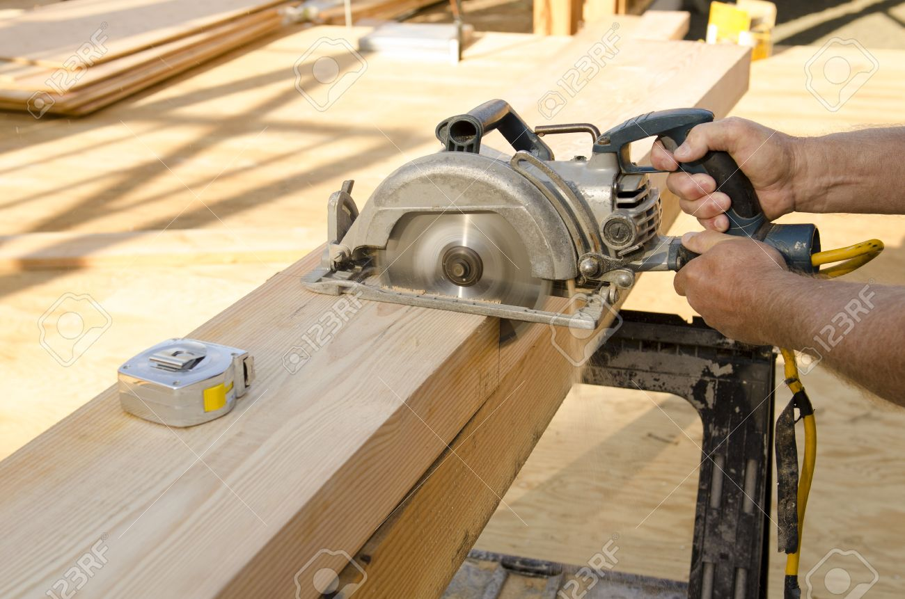 Framing construction contractor cutting a beam for a window header framing construction contractor cutting a beam for a window header on a wood frame wall of jeuxipadfo Choice Image