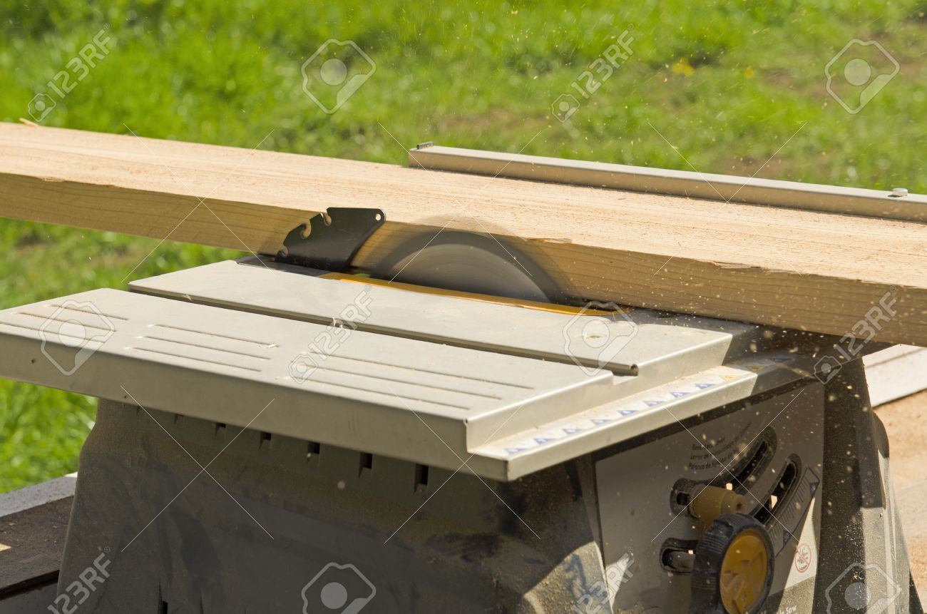 Stock Photo - Wood siding contractor using a table saw to cut window and door trim boards on the construction of a new home & Wood Siding Contractor Using A Table Saw To Cut Window And Door ...