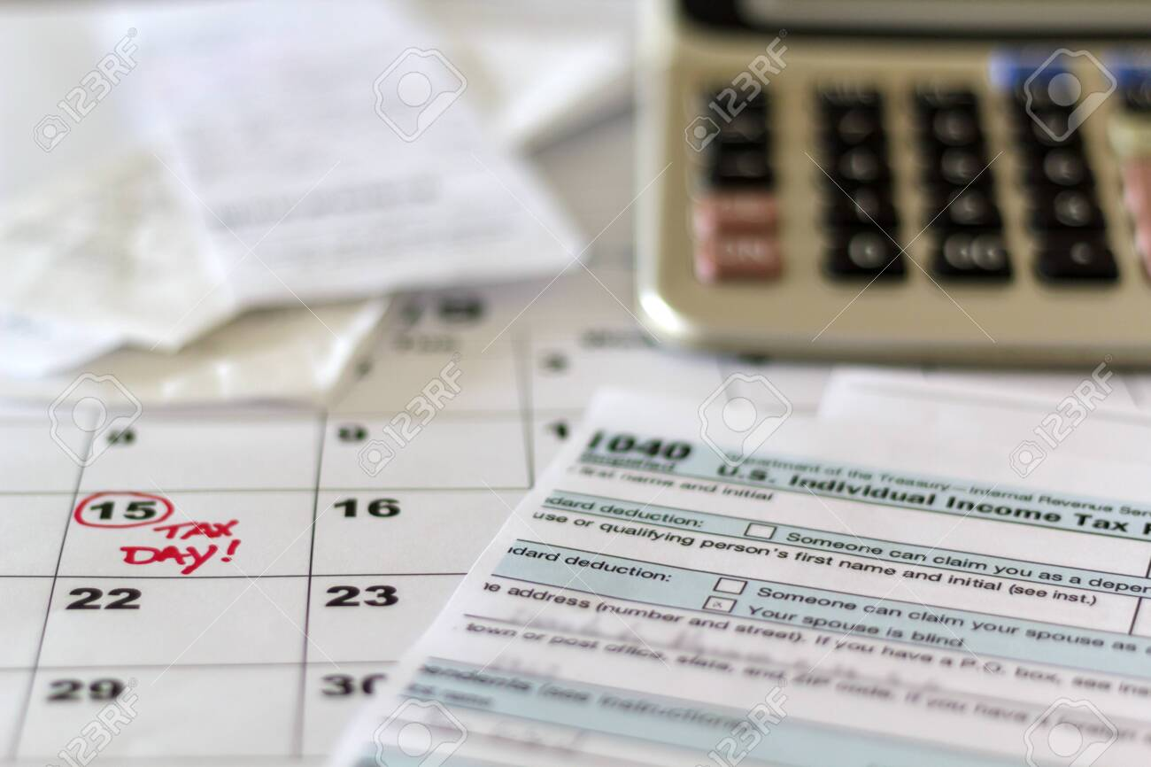 Desk with tax form, receipts, calculator and calendar. Financial Accounting Taxation Concept - 121428228
