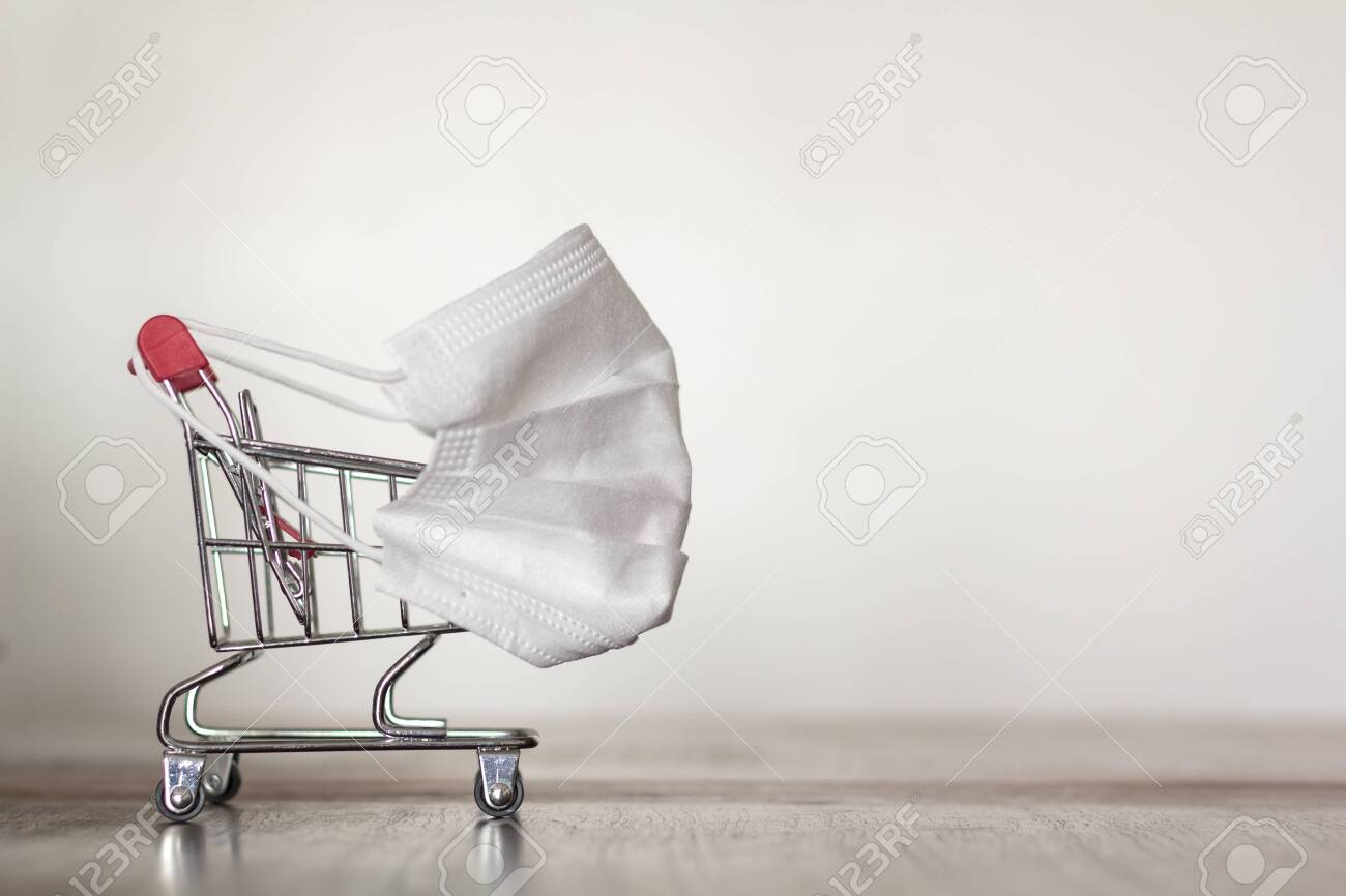 Shopping trolley with medical mask. Coronavirus pandemic, COVID-19 shopping concept. With copy space - 143222685