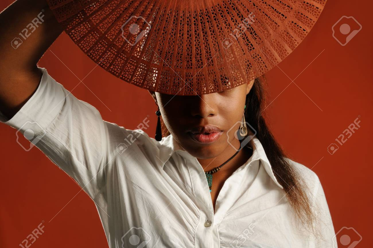 Portrait of young african fashion female covering face with a fan Stock Photo - 3478326