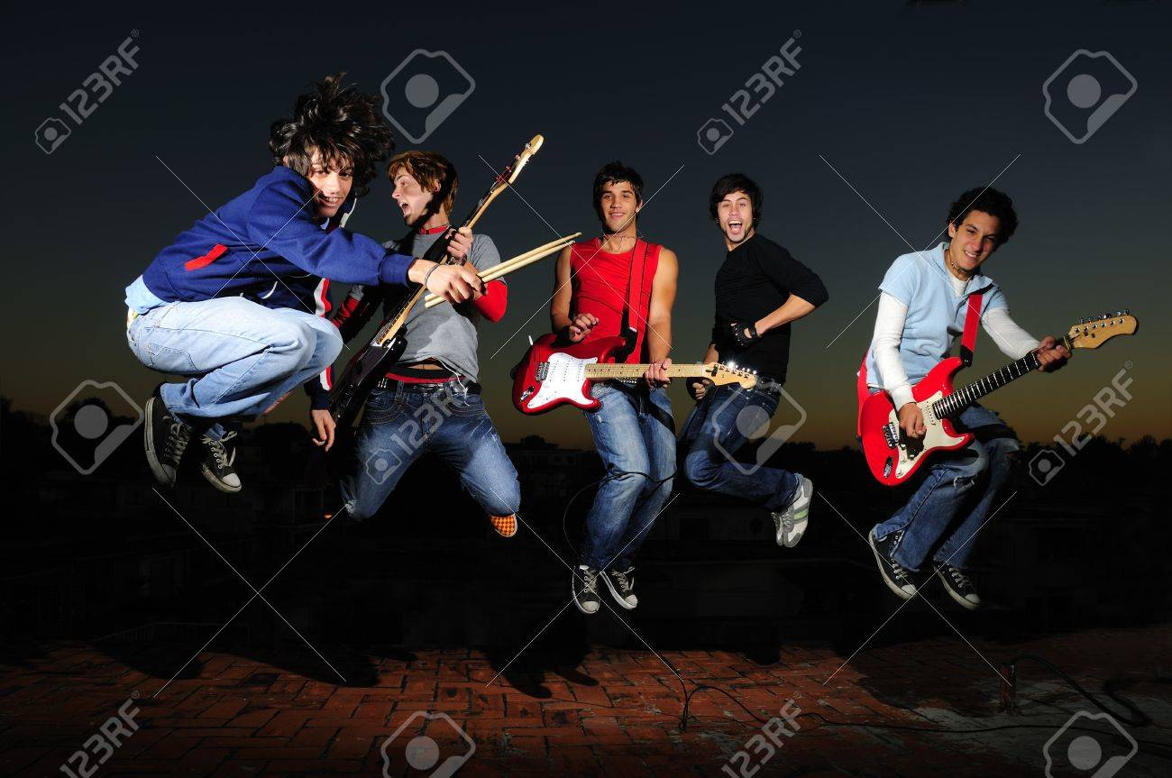 Portrait of young trendy teenager group jumping with musical instruments Stock Photo - 4011863