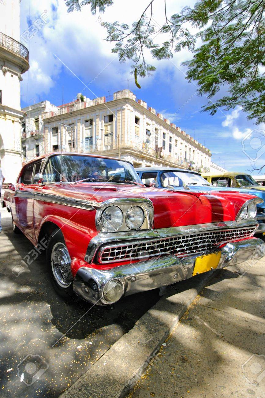 Old Red Car Parked Under Tree Branches In Havana Cuba Stock Photo