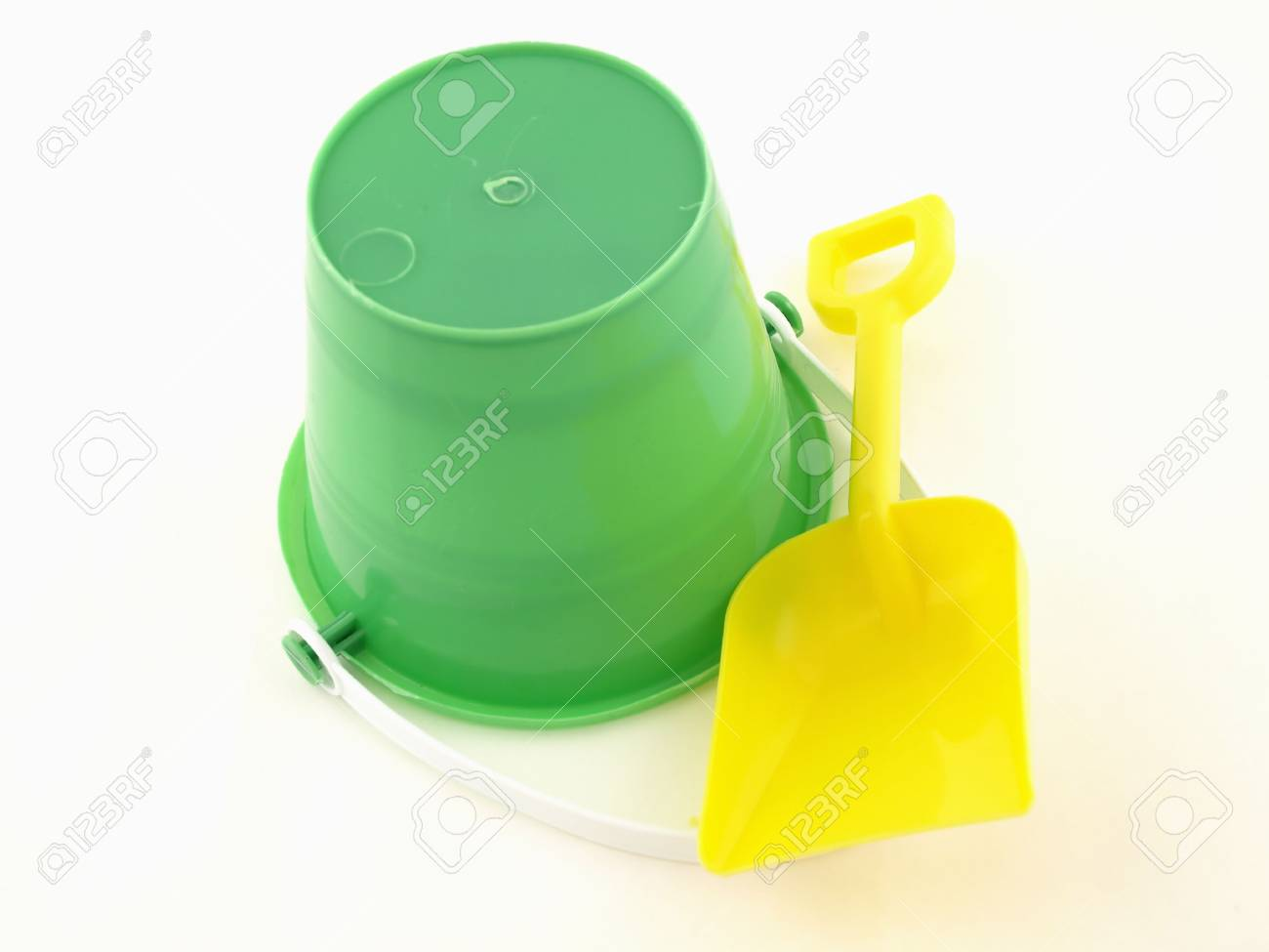 6e37675388341c A green plastic bucket upside down with a shovel isolated on a white  background Stock Photo