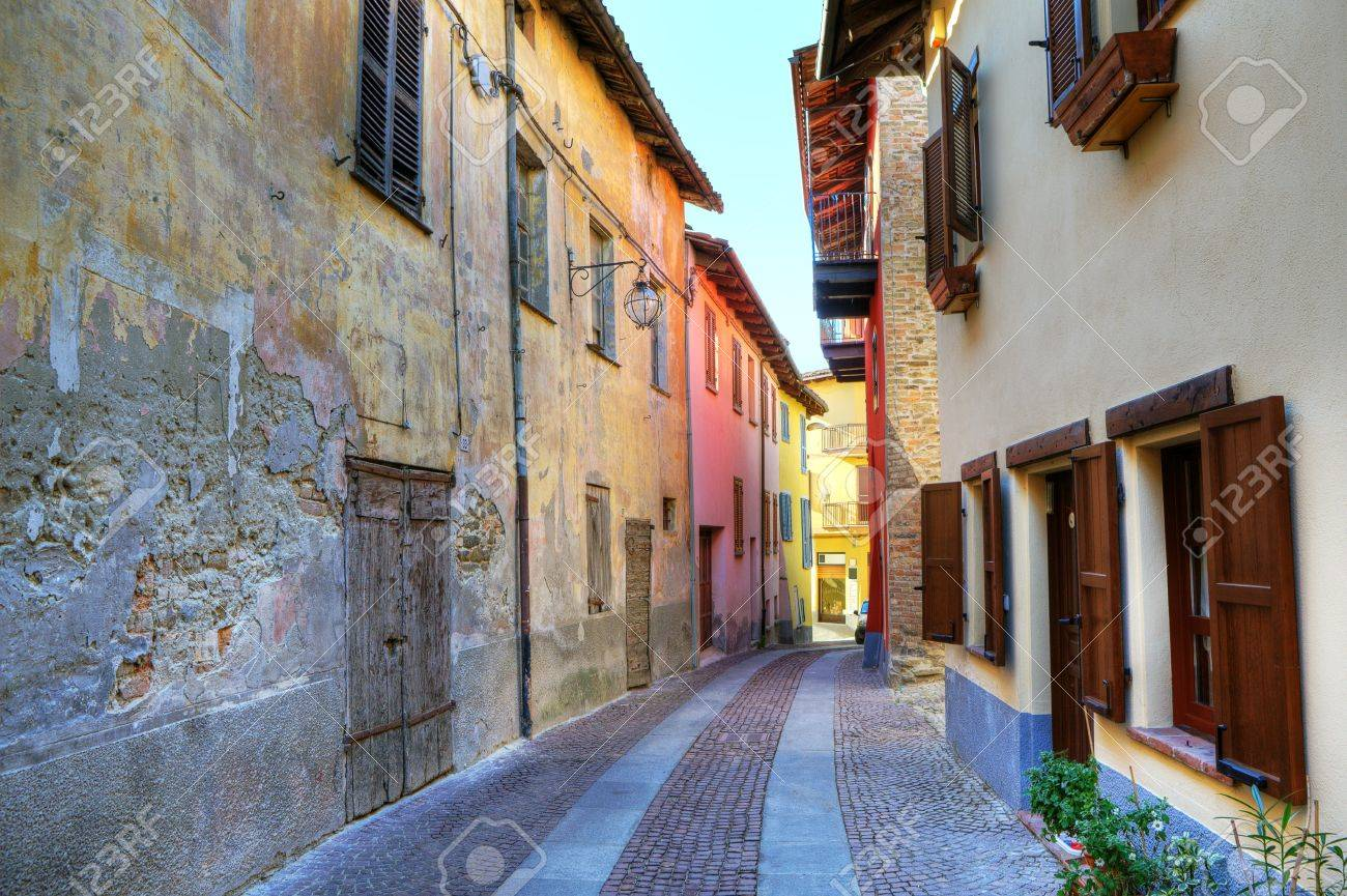 Narrow paved street among old abandoned house from one side and renovated from other in samll town of Serralunga D'Alba in Northern Italy. Stock Photo - 11962891