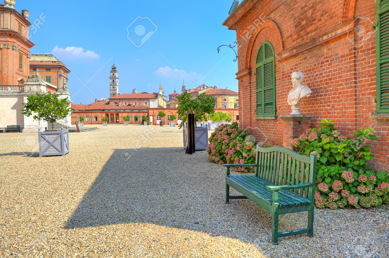 Stock Photo   Wooden Bench On The Gravel Pathway Next To Red Brick House At  The Entrance To Park And Royal Castle Of Racconigi In Piedmont, Northern  Italy